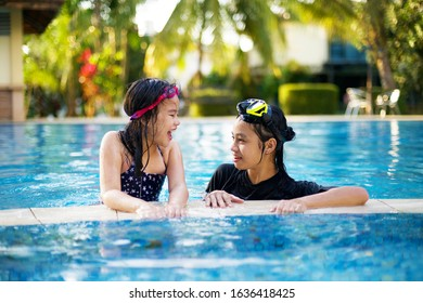 Two happy Asian girls laughing by resort poolside.Active children in swimming pool in nature resort.Healthy outdoor activity in summer Asia.Swimwear and goggles.