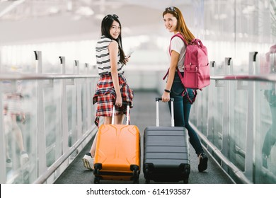 Two happy Asian girls traveling abroad together, carrying suitcase luggage in airport. Air travel or holiday vacation concept