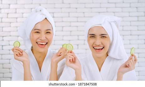 Zwei glückliche asiatische Mädchen in weißen Bademänteln mit Handtüchern auf den Köpfen, die Gurkenscheiben im Wohnzimmer halten.