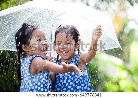 Two happy asian little girls with umbrella having fun to play with the rain together