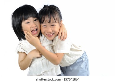Two happy asian little sisters hugging isolated on white background , siblings love together