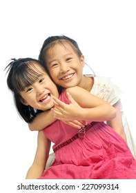 Two happy asian little sisters hugging isolated on white background, siblings love together