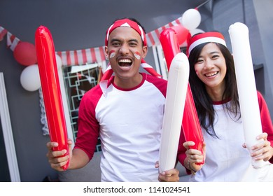 two happy asian people celebrating indonesia independence day