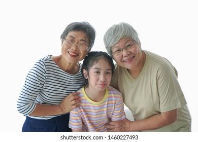 Two happy asian senior women  hugging a little girl.