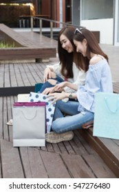 two happy asian shopaholic women with colorful shopping bags at department store shopping mall, blur background