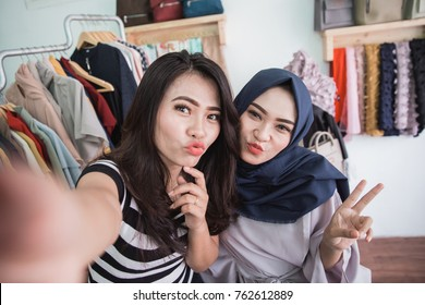 two happy asian woman in clothing store taking selfie together