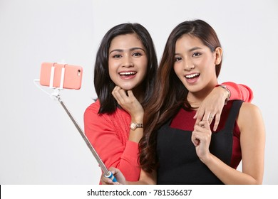 Two happy asian woman taking selfie together on the white background