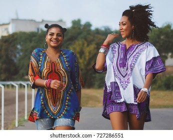Two happy beautiful afro-american women friends walking outdoor. Young mixed race girls wearing colorful clothing communicates, enjoys the meeting and laughing