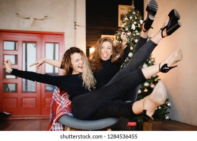 Two happy beautiful curly teen girls sitting in chair on Christmas tree background, legs up high heels, stuck out her tongue lifestyle sisterhood concept