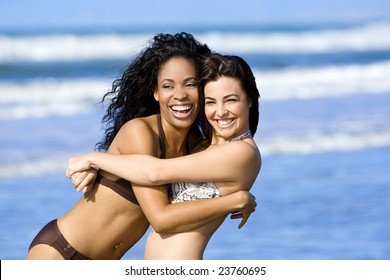 Two happy beautiful friends playing on the beach