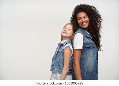 Two happy beautiful girls wearing family look while posing over white background, leaning their backs on each other and looking gently with cheerful smile
