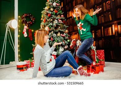 Two happy and beautiful sisters having fun near Christmas tree