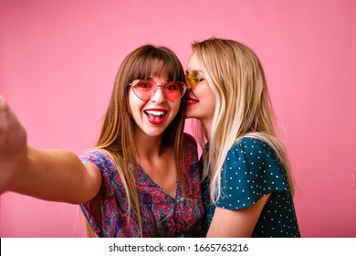 Two happy best friends sister women girls wearing trendy spring summer printed bright vintage dresses and sunglasses, making selfie, kissing to the cheek, perfect relationship, pink studio background.