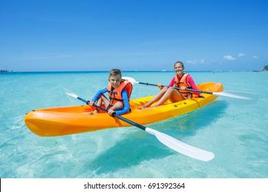 Two happy boy and girl kayaking at tropical sea on yellow kayak