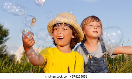 two happy boy play in bubbles outdoors