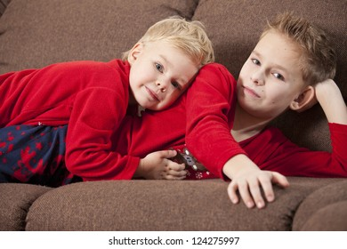 Two happy boys embracing, lying on the sofa
