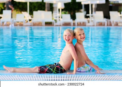 Two happy boys, laughing teenage twin brother, enjoying sunny summer vacation playing in outdoors swimming pool