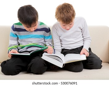 Two happy boys reading big book isolated on white background