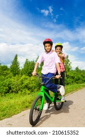 Two happy boys riding same bike both standing