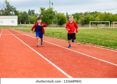 two happy boys running on sports tracks in the stadium