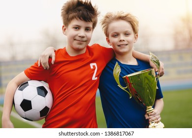 Two happy boys soccer players holding soccer ball and golden trophy. Children football players on the field in red and blue jersey sportswear