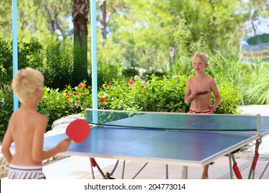 Two happy boys, teenager twin brothers, enjoying summer vacation playing ping pong outdoors