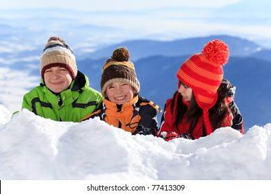 Two happy brothers and sister in woolly hat on snow mountainside in Winter.