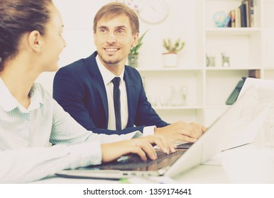 Two happy business male and female assistants wearing formalwear working using laptops in company office. Focus on the man