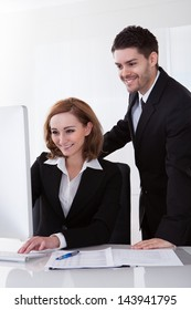 Two happy business partners looking at computer