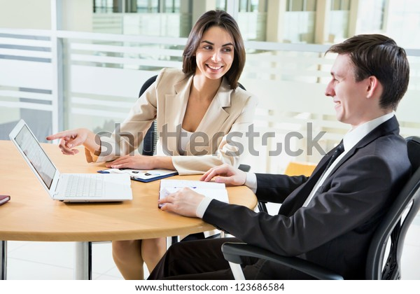 Two happy business people in a meeting at office