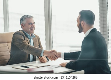 The two happy businessmen handshaking over the glass in the office