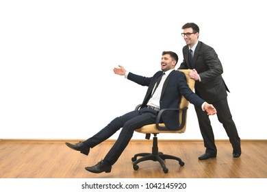 The two happy businessmen ride on the chair on the white wall background