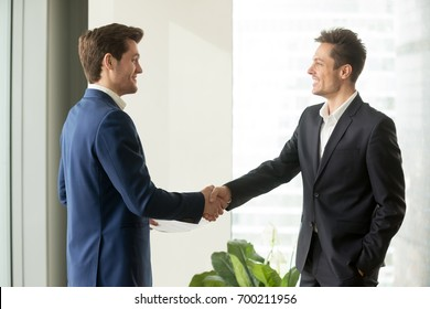 Two happy businessmen shaking hands standing in office, smiling partners handshaking, thanking for support, reaching agreement, sealing good business deal, forming good friendly business relations