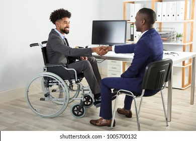 Two Happy Businessmen Sitting On Wheelchair And Chair Shaking Hands In Front Of Computer