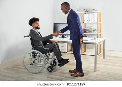 Two Happy Businesspeople In Office Shaking Hands