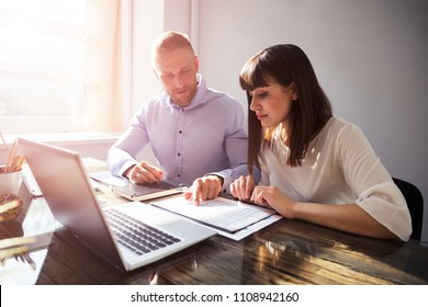 Two Happy Businesspeople Working On Document With Laptop On Desk