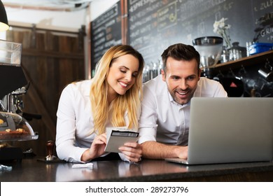 Two happy cafe managers working on laptop