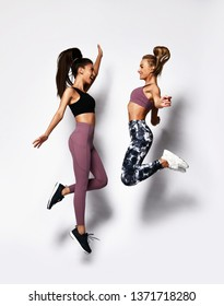 Two happy carefree young sport women jumping dancing laughing on white background