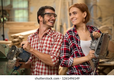 Two happy carpenters looking at each other, smiling and posing. Joiners holding tool for machining wood in hands. Beautiful woman with ginger hair and man in safety glasses wearing checked shirts.