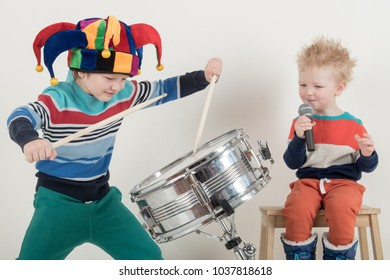 Two Happy Caucasian child drummer in a carnivalous fool's cap plays on a new drum set. Parents bought the boy a drum for training. Kids in bright clothes with new sticks in his hands be happy at home