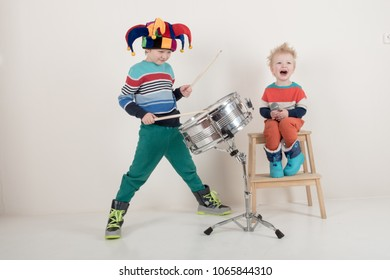 Two Happy Caucasian child drummer in carnivalous fool's cap plays on new drum set. Parents bought the boy a drum for training. Kids in bright clothes with new sticks in his hands be happy at home