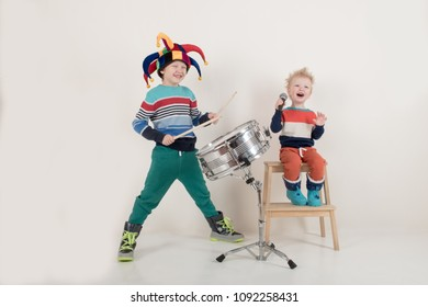 Two Happy Caucasian child drummer in carnivalous fool's cap plays on new drum set. Parents bought boy drum for training. Kids in bright clothes with new sticks in his hands be happy at home