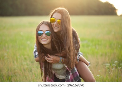 Two happy cheerful girl under the light of sunset. best friends