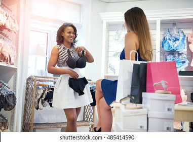 Two happy chic young woman shopping for lingerie in a clothing boutique with one holding up a bra and panties to her body as they decide whether to purchase