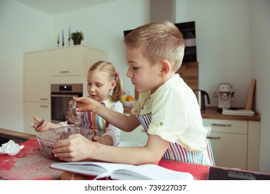 Two happy children baking christmas cookies at modern kitchen