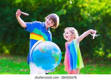 Two happy children, cute curly toddler girl and a smiling school age boy play with toy airplanes flying over the globe dreaming of traveling around the world. Kids fly and travel with airplane.