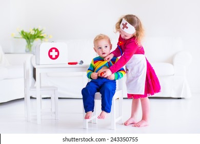 Two happy children, cute toddler girl and adorable baby boy, brother and sister, playing doctor and hospital using stethoscope toy and medical uniform, having fun at home or preschool