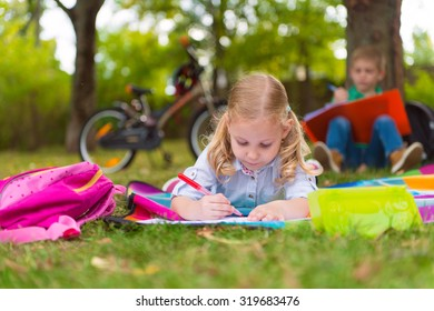 Two happy children  drawing in summer park