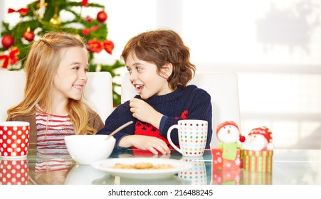 Two happy children eating cookies at christmas at the table