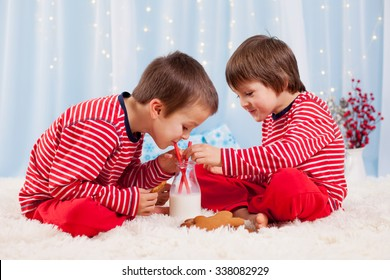 Two happy children eating cookies at christmas and drinking milk, laughing and talking, having fun